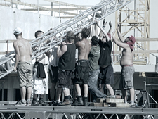 9 stagehands work in the sun on a stage